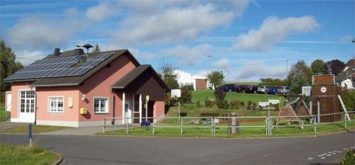 Bild: Mehrzweckgebäude mit Kinderspielplatz